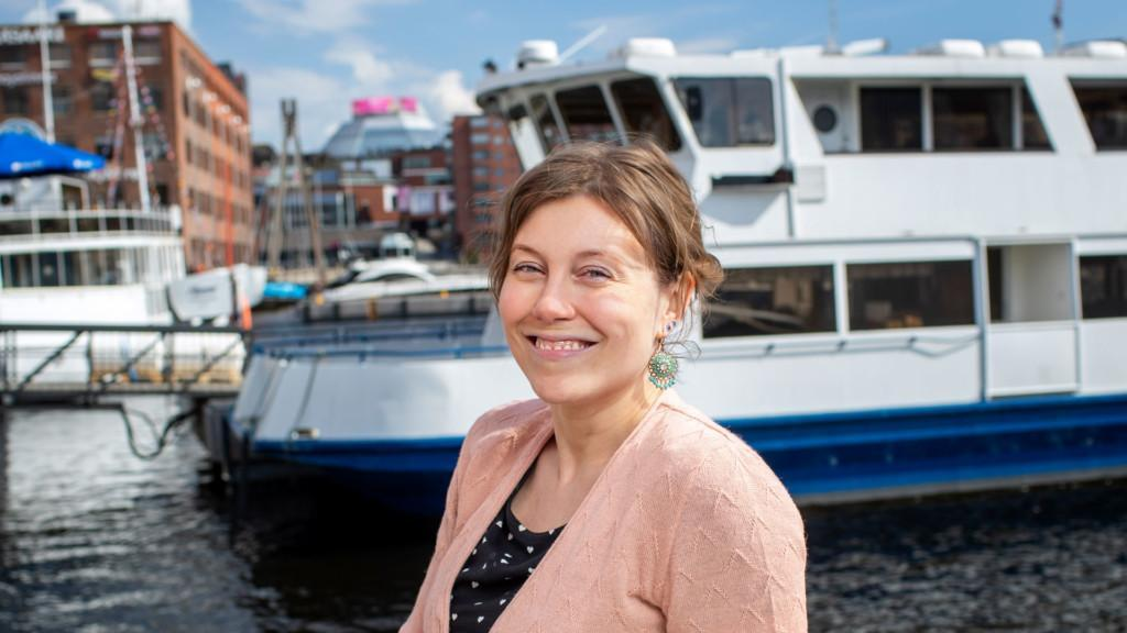 Etualalla Katja Vaulio vaaleanpunaisessa villatakissa. Taustalla veneitä ja ranta, jossa punatiilisiä rakennuksia.